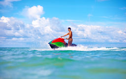 Joyful man riding jet ski, tropical ocean, active vacation Royalty Free Stock Photos