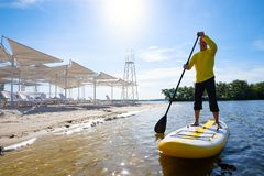 Joyful man sails on a SUP board in large river along the beach. And enjoying life. Stand up paddle boarding - awesome active outdoor recreation. Wide angle royalty free stock photo