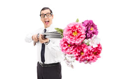 Joyful man shooting flowers from a shotgun Stock Photos