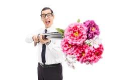 Joyful man shooting flowers from a shotgun. Isolated on white background Stock Photos