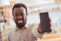 Joyful man showing his new phone in coffeehouse Stock Images