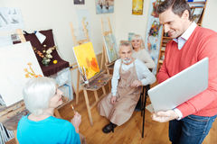 Joyful man showing laptop to colleagues in painting studio Stock Images