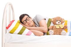 Joyful man sleeping in a bed with a teddy bear Royalty Free Stock Photo