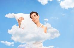 Joyful man sleeping up in clouds in the sky Stock Photo
