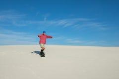 Joyful man slides down on a snowboard on the sand dune royalty free stock photography