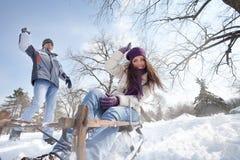 Joyful man throwing snowball at woman. Young men throwing snowball at his girlfriend, fun in snow Royalty Free Stock Photo