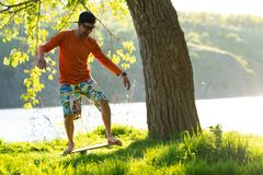 Joyful man is training on the balance board. Joyful bearded man is training on the balance board and having fun on a green meadow next to river on sunny evening Royalty Free Stock Images