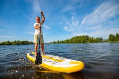 Joyful man is training SUP board. In large river on a sunny morning against a blue sky background . Stand up paddle boarding - awesome active outdoor recreation royalty free stock photos