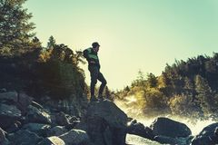 Joyful man travel mountains. Picturesque location in Europe. Mountains and sea view. Young traveler guy standing on a stone on the royalty free stock images
