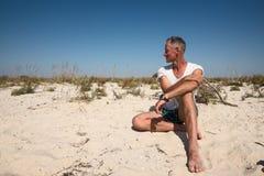 Joyful man traveler sits on the deserted seashore Royalty Free Stock Photo