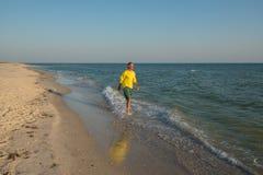Joyful man traveler is walking along the surf line Stock Photo