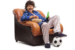 Joyful man watching football on TV. Seated in an armchair and eating popcorn isolated on white background Royalty Free Stock Photography