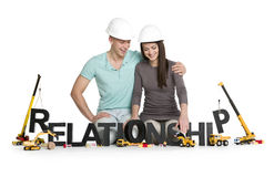 Joyful man and woman building relationship-word. Working on relationship concept: Happy young men and women developing the word relationship along with Royalty Free Stock Image