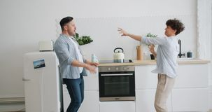 Joyful man and woman in casual clothing dancing laughing in kitchen in apartment stock footage