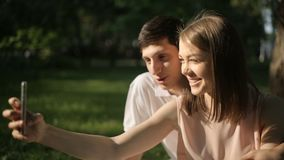 Joyful man and woman doing selfie phone. Happy boy and girl photographed themselves on the phone stock video footage