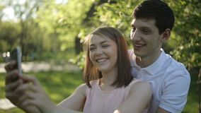 Joyful man and woman doing selfie phone. Happy boy and girl photographed themselves on the phone stock video