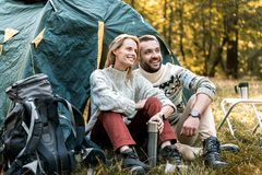 Joyful man and woman relaxing in forest. Wonderful day for rest. Portrait of happy loving couple enjoying nature in autumn. They are sitting near tent and Royalty Free Stock Photo