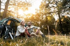 Joyful man and woman resting in nature together. Happy moments. Cheerful loving couple is talking and laughing while relaxing in the forest. They are sitting Royalty Free Stock Image