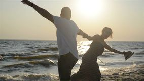 Joyful Man and Woman Swirling on the Beach Holding Hand in Hand and Smiling.