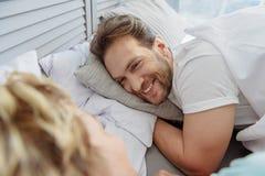 Joyful married couple lying in bedroom Stock Images