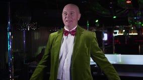 Joyful mature Caucasian man in green jacket spinning and singing next to music controller. Senior male DJ working in