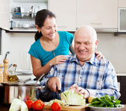 Joyful mature couple cooking food Stock Photography