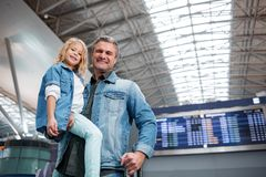 Joyful mature father and daughter are waiting for flight. Family travelling. Low angle portrait of positive middle-aged men is holding his little child while Stock Photo