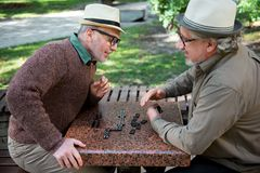 Joyful mature friends relaxing with intellectual game outdoor stock photography