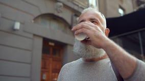 Joyful mature guy drinking coffee outdoors stock footage
