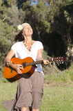 Joyful mature hippie woman with guitar Royalty Free Stock Photography