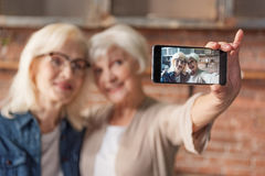 Joyful mature ladies making selfie in kitchen. Happy old women are photographing themselves on mobile phone at home. They are embracing and smiling. Focus on stock photography
