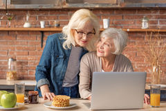 Joyful mature ladies using modern computer. Carefree old women are reading recipe of healthy food in internet. They are looking at laptop and smiling. Friends royalty free stock photography