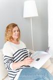 Joyful mature lady reading journal at home Stock Photos