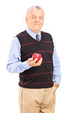 Joyful mature man holding an apple Royalty Free Stock Images