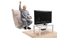 Joyful mature man in pajamas seated in an armchair watching soccer on TV and holding his hand up. Isolated on white background royalty free stock photo