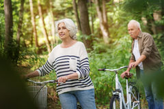Joyful mature man and woman cycling in park royalty free stock images