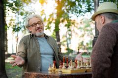 Joyful mature men enjoying chess entertainment royalty free stock photos