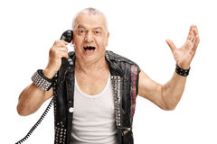 Joyful mature punk talking on telephone. Mature man in an old punk jacket talking on telephone and gesturing with his hands isolated on white background Royalty Free Stock Images