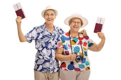 Joyful mature tourists holding passports. Isolated on white background Royalty Free Stock Images