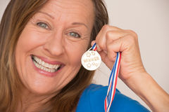 Joyful mature woman with medal Royalty Free Stock Photo
