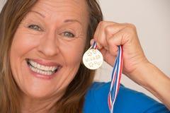 Joyful mature woman presenting medal Stock Image