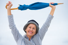 Joyful mature woman with umbrella arms up Stock Photography