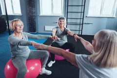 Joyful mature women holding hands while exercising with fitness balls. Sport is power. Motivated elderly ladies sitting on fitness balls and holding their hands Royalty Free Stock Image