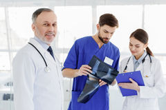 Joyful medical team examining human bone on radiograph Royalty Free Stock Image