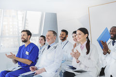 Joyful medical team greeting their colleague by applauds Royalty Free Stock Image