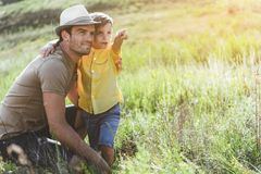 Happy young family resting on nature. Joyful men on meadow embracing his little son, kid is pointing somewhere. Copy space in right side Stock Photo