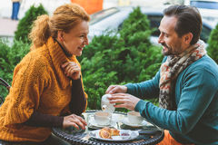 Joyful middle-aged lovers drinking hot beverage royalty free stock images