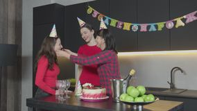 Caring mom bettering hats to daughters at Birthday. Joyful middle aged mother adjusting party hats to lovely daughters, preparing celebration of Birthday at home stock video footage