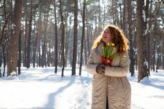 Curious smiling woman looking up with snowy forest on the background stock photo