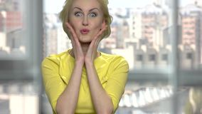 Joyful middle-aged woman fooling around. Happy blonde woman making funny faces. Window city background stock video
